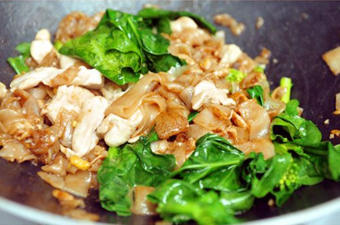 Pad See Ew is a noodle dish made by stir frying wide rice noodles with ...