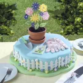 "If mom has a green thumb, celebrate her special day with A Planter's Paradise. This cake pays homage to mom's favorite activity with details like a ""dirt""-filled flower pot, a trowel, and a white picket fence."
