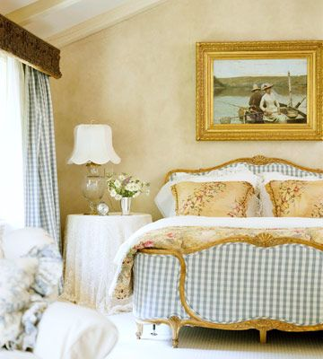 There's an inherent sense of romance in a French country styled room. This bedroom from Better Homes & Gardens has gilded edges on the furniture, blue & white gingham, and a touch of lace.