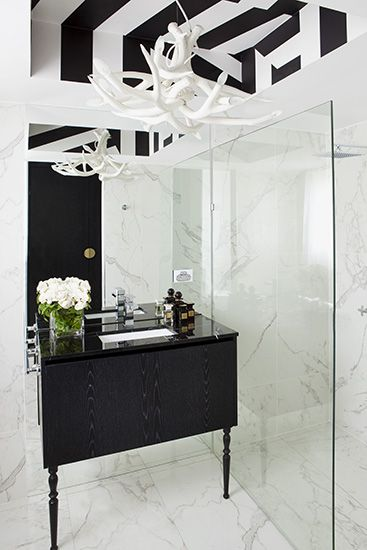 A 70's Apartment Gets a Bold Black and White Makeover // Chandelier and marble tile