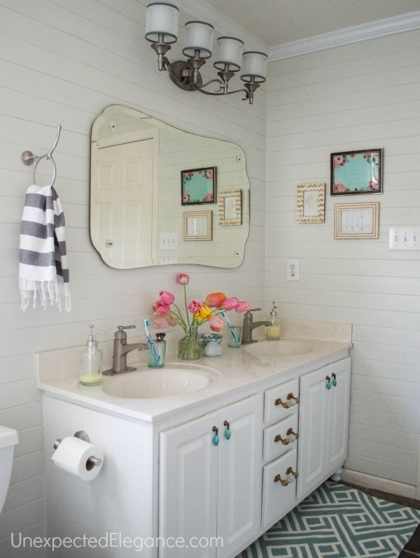 A bathroom makeover on a BUDGET! Find some great tips to makeover a builder grade, boring bathroom without spending a fortune! Lots of DIY projects on a budget and ideas to freshen up your space.
