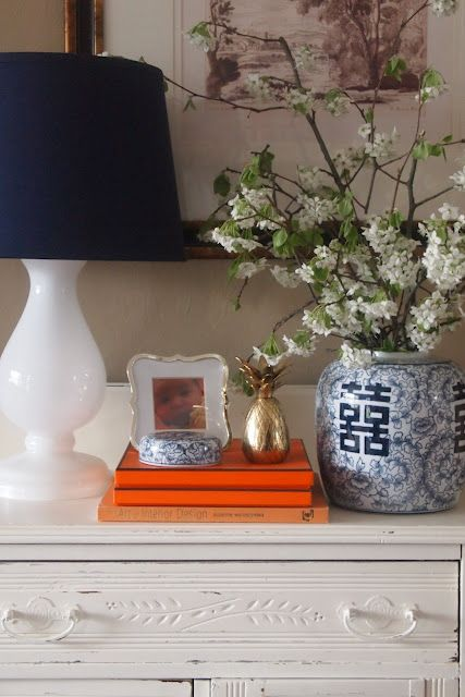 The branches in the blue & white vase are great & the orange books add some unexpected color, but I feel the lamp is too white against the white chest & the shade is much too dominant.