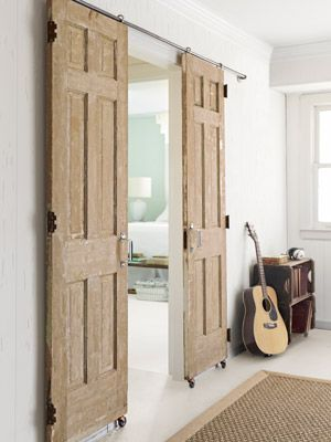 """Emily set her sights on using a pair of yard-sale doors to fashion a sliding barn-style entrance to the home office. She balked upon discovering that """"the track alone cost a couple of hundred dollars,"""" so she substituted casters and plumbing pipes for the expensive kit.    Office doors, $78: Fifty-eight dollars' worth of hardware—including casters and plumbing pipes—transformed two salvaged $10 doors into a barn-style entry."""