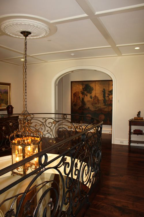 Upstairs landing and hallway with detailed ceiling and gorgeous railing.
