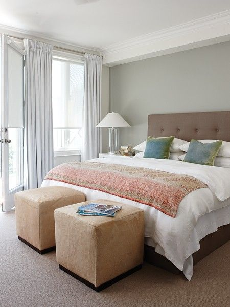 Lovely bedroom with gray walls and light gray linen curtains layered over white roller shades. Taupe tufted headboard and bed filled with green and blue pillows and pink and gray throw blanket. Suede cube ottomans sit at foot of bed whilst white nightstand holds clear glass column lamp.