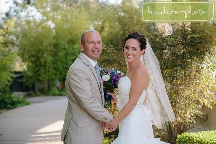 bride & groom - tan suit, veil, purple & blue floral bouquet
