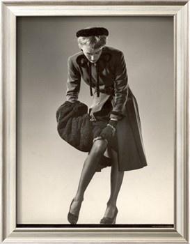 Model Wearing Black Stockings, Fitted Dress Coat, Fur Trimmed Hat and Fur Muff Adjusting Garter