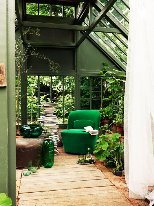 Love the emerald green velvet chair and billowing curtains amongst the lush greenery