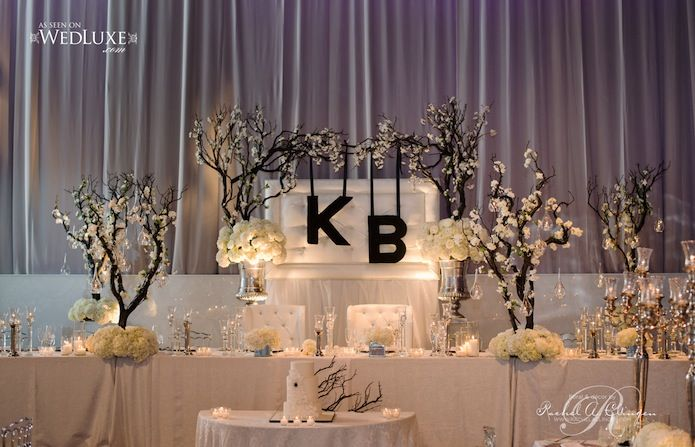 Beautiful head table with custom archway created with manzanita trees