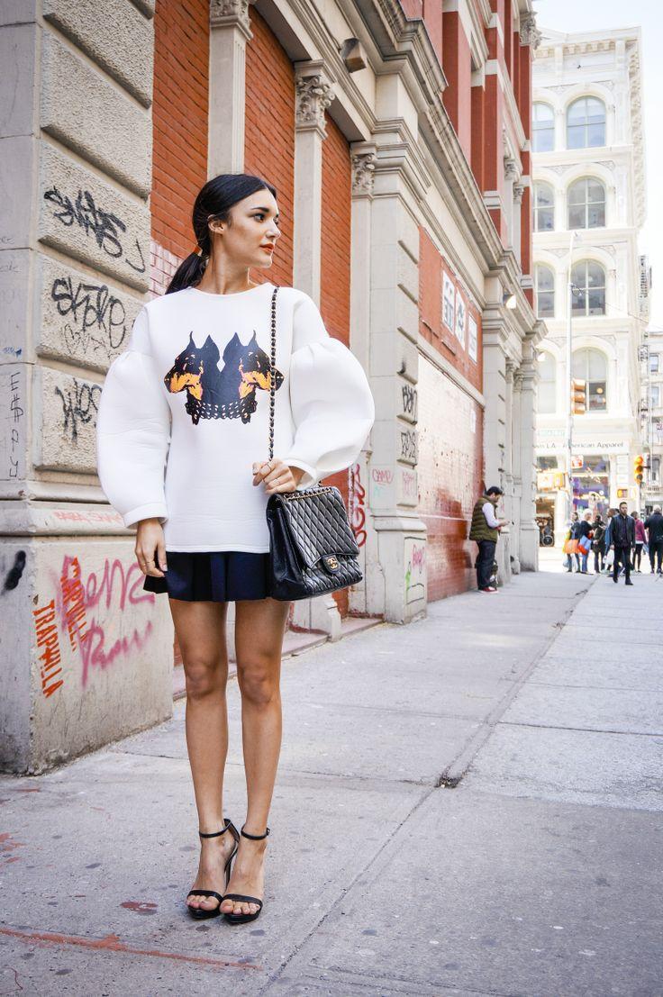 Style blogger Anisa Sojka wearing oversized white Rottweiler dog sweater, black Bershka skirt, black sandal Zara heels, black gold chain Chanel crossbody bag, street style fashion taken in New York City