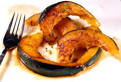 Baked acorn squash in the oven with brown sugar and rosemary