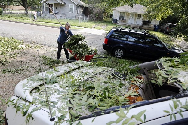 Peggy Jones cleans up around her damaged car. (G.J. McCarthy/The Dallas Morning News)