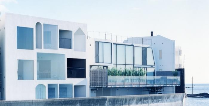 The north-facing facade has floor-to-ceiling windows that abut the harbor wall.