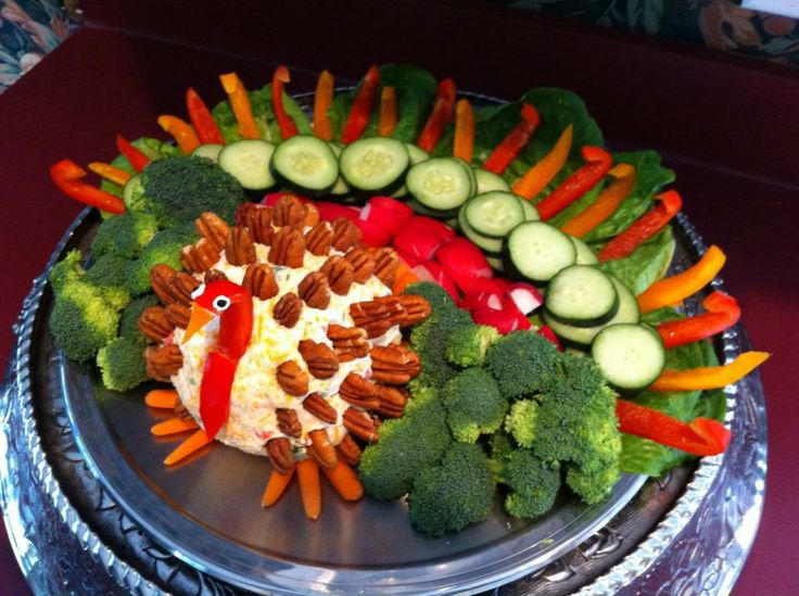 Thanksgiving turkey cheese ball and veggie tray (turkey made with pecans, cut red and orange pepper, cream cheese eyes with black frosting, and mini carrot feet)