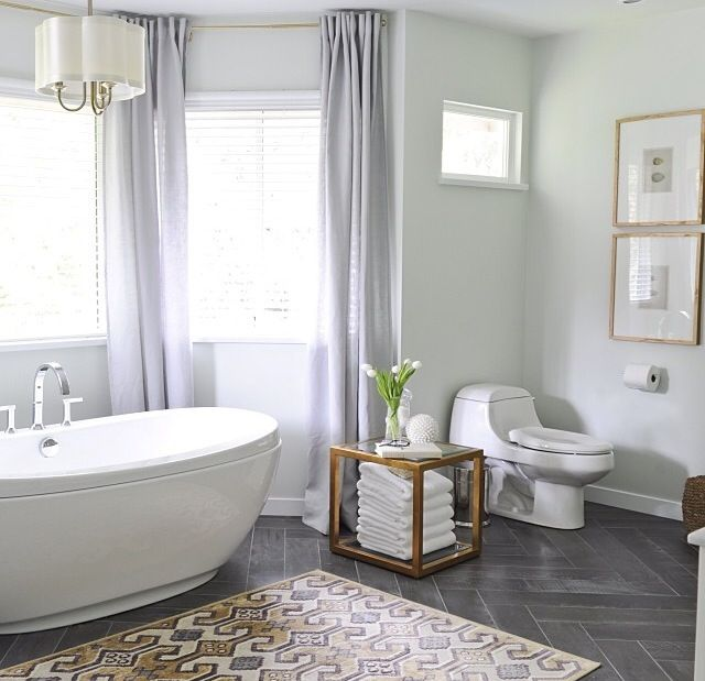 master bath. light grey. area rug. gold picture fraes. gold fixture. chevron floors. gold curtain rod. tub faucet.