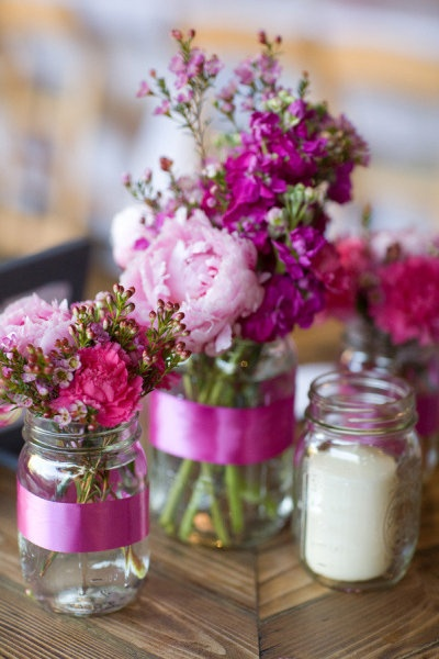 glass jars wrapped in ribbon used as centerpiece vases