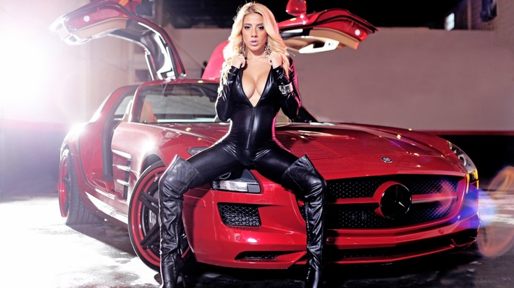 Sexy girl in a latex suit posing with a smoking hot Mercedes SLS