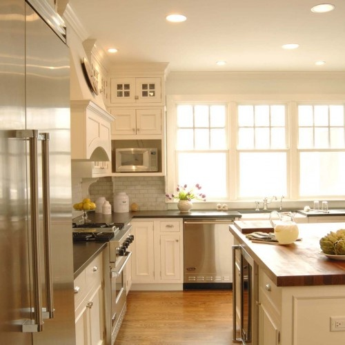 windows, sink, white subway tile with darker countertop; glass cabinets on top