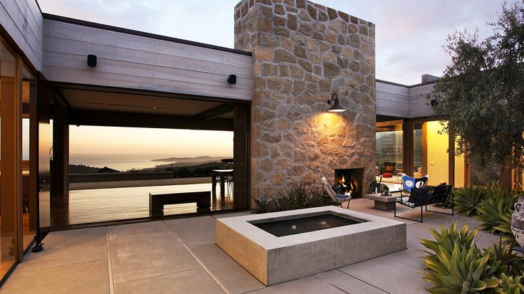 Real Estate Envy: 7 Dreamy Vacation Homes // water fountain, butterfly chairs, outdoor fireplace, courtyard