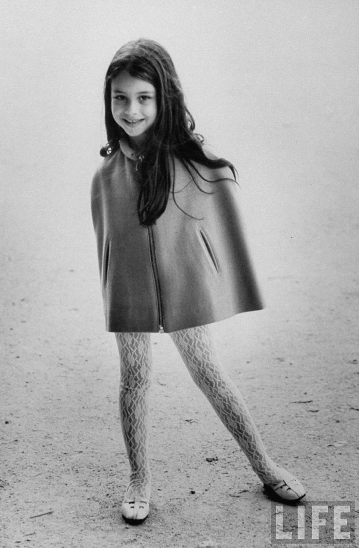 A little girl modeling a waist cut two-pocket sleeve-less jacket with flowered white tights and white shoes, by Pierre Cardin . Paris . June 1967 . Photo by Pierre Boulat