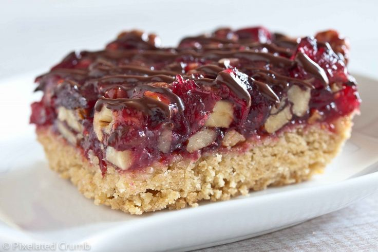 cranberry turtle bars with gooey caramel, pecans and chocolate on a ...