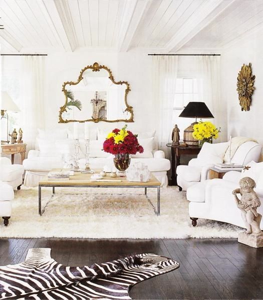 beautiful white walls, white sofa and chairs and shag rug