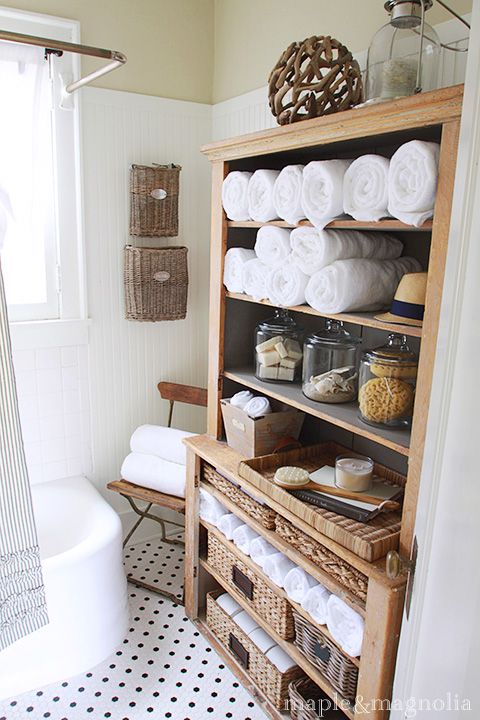 Hutch in the bathroom. Love! Natural materials and white. Curved tub, polka dot floor.