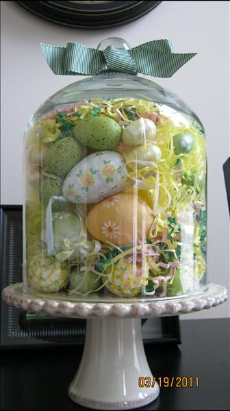 Willow House cloche stuffed with Easter eggs large and small, yellow Easter grass tied up with a grossgrain green ribbon set atop the Villa Petite Pedestal!