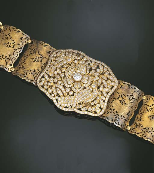 A DIAMOND AND GOLD BUCKLE AND GOLD PANEL BELT    The lobed rectangular openwork buckle designed as a pierced diamond-set flower with a circular-cut diamond centre weighing 4.87 carats, to the centre of old and circular-cut diamond peacock and butterfly amidst foliage and blossoms, to a belt composed of seventeen gold panels each pierced and engraved depicting a Chinese lion amidst foliage, buckle 9.8 cm. wide, belt 72.0 cm. long