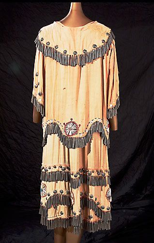 Pictured is the back of the Anishinaabe Indian dress on display at the Runestone Museum in Alexandria and recently featured in American Indian Art Magazine. The dress, circa 1930, is of faded red cotton sateen, adorned with dentalium shells, glass beads, metal conches and hand-rolled tin can cones with red printed labeling still visible on the inside. (Contributed photo by Mark Proudfoot) Alexandria Echo Press | Alexandria, Minnesota