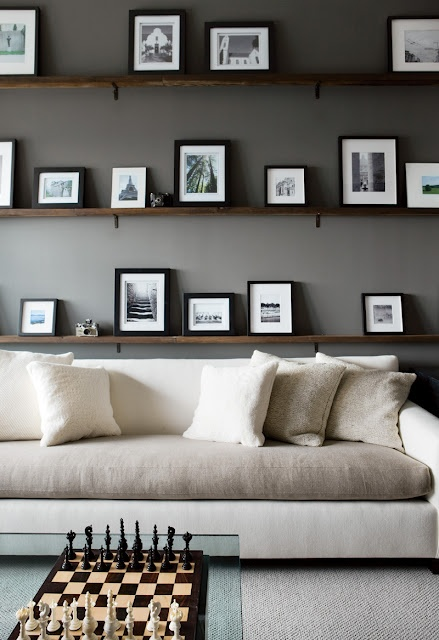 Paint the back of the bookcases with a flat dark gray.  Strip the shelves and stain dark.  Add pictures all in black frames and white mats.