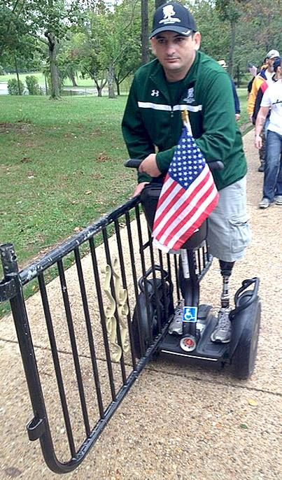 PICTURE OF THE DAY:  #VetMarch double-amputee veteran on a Segway, carrying one of the memorial barricades to the WhiteHouse gates.
