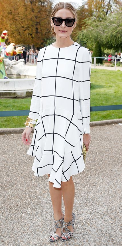 Olivia Palermo a graphic white-and-black windowpane-print dress with a flouncy hem. She styled her look with a gold cuff, black shades, a gold clutch, and printed strappy heels. #InStyle