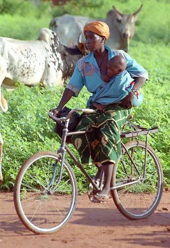 Anwar Olango Noted: the bike has no brakes, she directs it with one hand,with the other holding the baby, above all she is breastfeeding and riding uphill. Skilled.