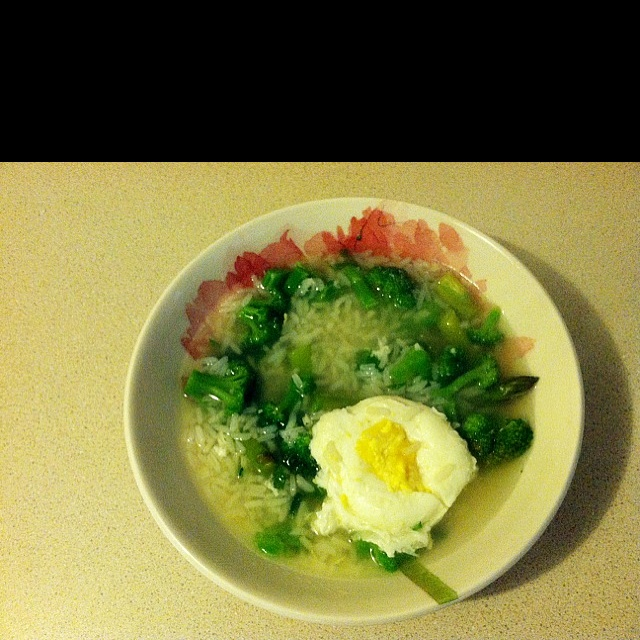 Chicken flavored rice soup with poached egg and veggies