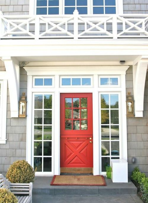 A bright splash of color on your home's front door is a great way to add interest to a traditional cedar shake and white Hamptons color scheme. Repeat the theme on the garage with carriage house style garage doors with a crossbuck pattern and windows.