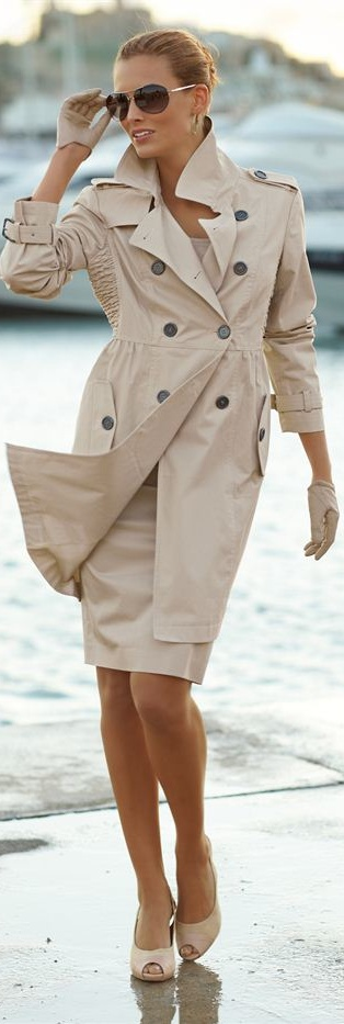 Classic beige trench (with a funky princess cut) over matching dress, shades & peep toe pumps. She is even sporting gloves. What a feminine power look!!!