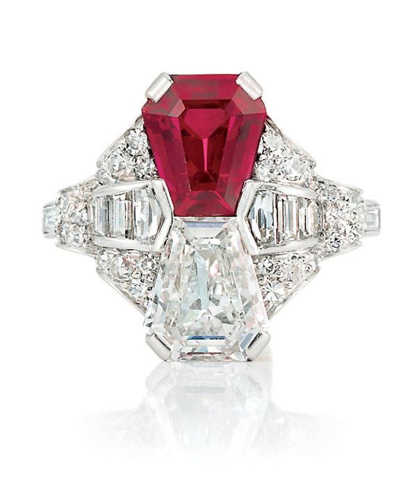 Art Deco Platinum, Ruby and Diamond Ring   Set with one shield step-cut ruby approximately 2.01 cts., and one shield step-cut diamond approximately 1.40 cts., flanked by 8 baguette and fancy-shaped diamonds, set with 50 single-cut diamonds, circa 1920