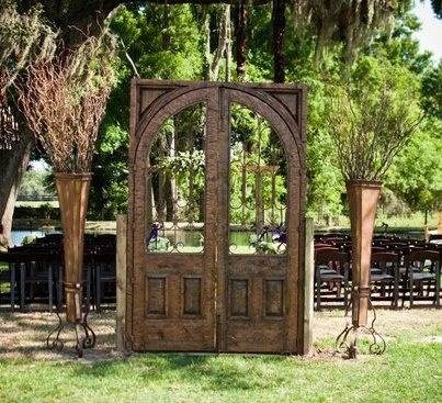 A stunning wood arch door and tall grapevine arrangements make quite the outdoor wedding entrance