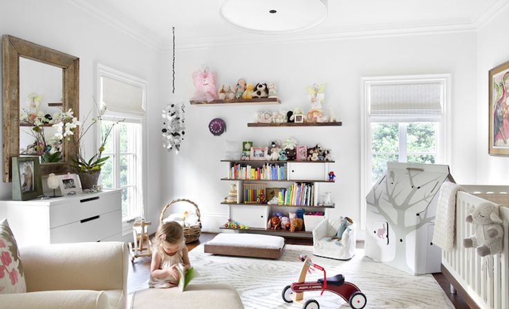 white modern white nursery design with white modern crib, white ribbed roller shade, white bookcase, rustic floating shelves, wood mirror, white modern dresser, ivory glider & ottoman and faux bois white & gray rug.