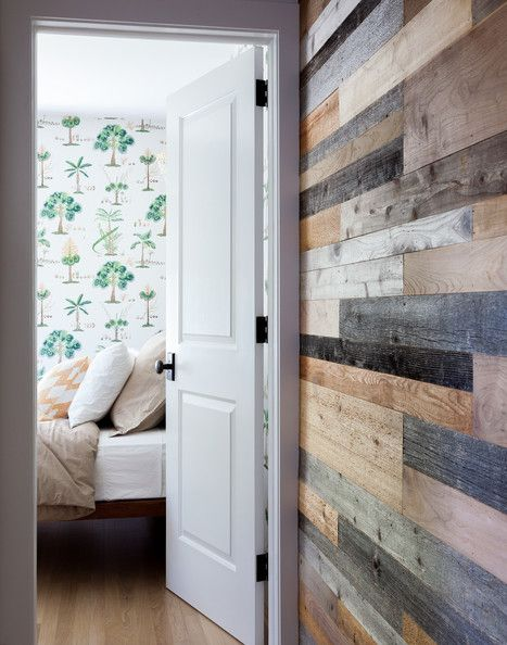 A hallway wall of mixed natural woods leading to a tree-motif wallpaper in a bedroom.