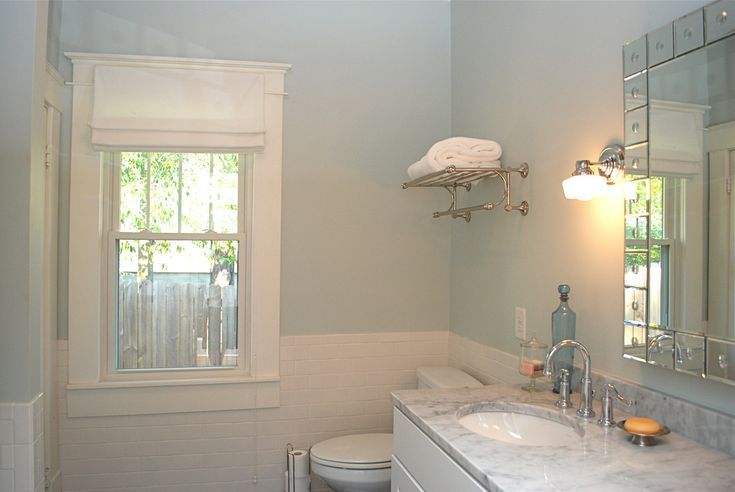 BM Silver Crest   source: The Estate of Things    Beautiful blue bathroom with heavenly blue walls paint color paired with white subway tile bathroom backsplash and white bathroom roman shade. White bathroom cabinets paired with Carrera marble countertops, glass block bathroom mirror and above the toilet towel holder.