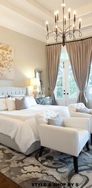 White and gray linens in bedroom with sitting area. Two tier ceiling and simple chandelier.