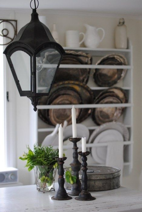 dark lantern in front of plate rack with ironstone and tarnished silver trays