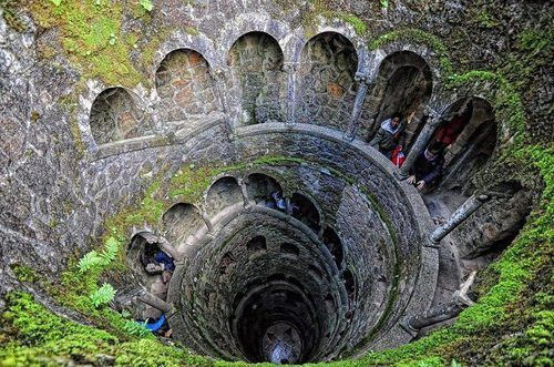 The Inverted Tower - Sintra, Portugal  An underground tunnel with a spiral staircase, supported by carved columns, down to the bottom of the well through nine landings. The nine hole round landings, separated by fifteen steps, evoke references to Dante's Divine Comedy, and may represent the nine circles of hell, paradise, or purgatory. The well is connected to laberíticas caves that lead to a spooky garden surrounded by a lake. The land that is now Quinta da Regaleira had many owners throug