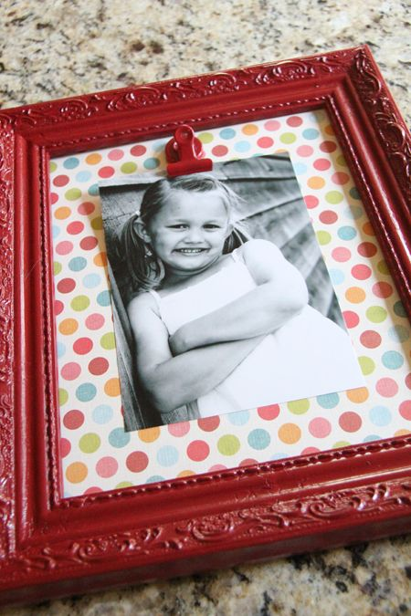 LOVE this idea: Spray paint a cheap frame, scrapbook paper in frame, hot glue a metal clip, change out photos as often as you want.