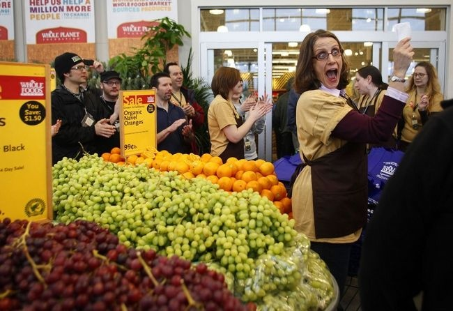 Danielle Neumann welcomes customers to the new Whole Foods Market in Lynnwood as the store opens its doors to the public for the first time. (Photo by Mark Mulligan, The Herald)