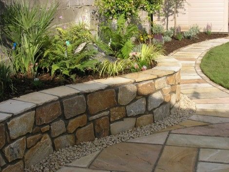 curved raised planting bed - love the stonework and paving for walling ...