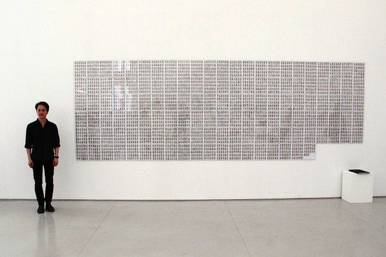 """Artist Rutherford Chang stands next to """"The Class of 2008.,"""" a collection of alphabetized hedcuts from The Wall Street Journal, at the White Space Gallery in Beijing."""