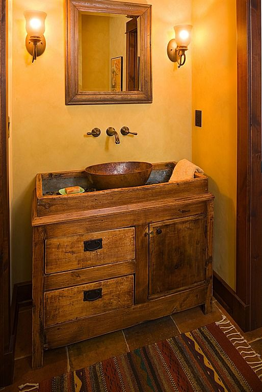 A bronze bowl sits in the center of a rustic vanity for an antique-country feel.